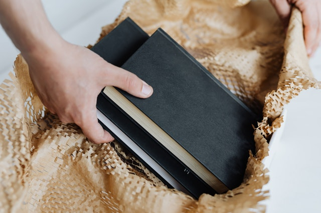 A hand wrapping books in brown paper
