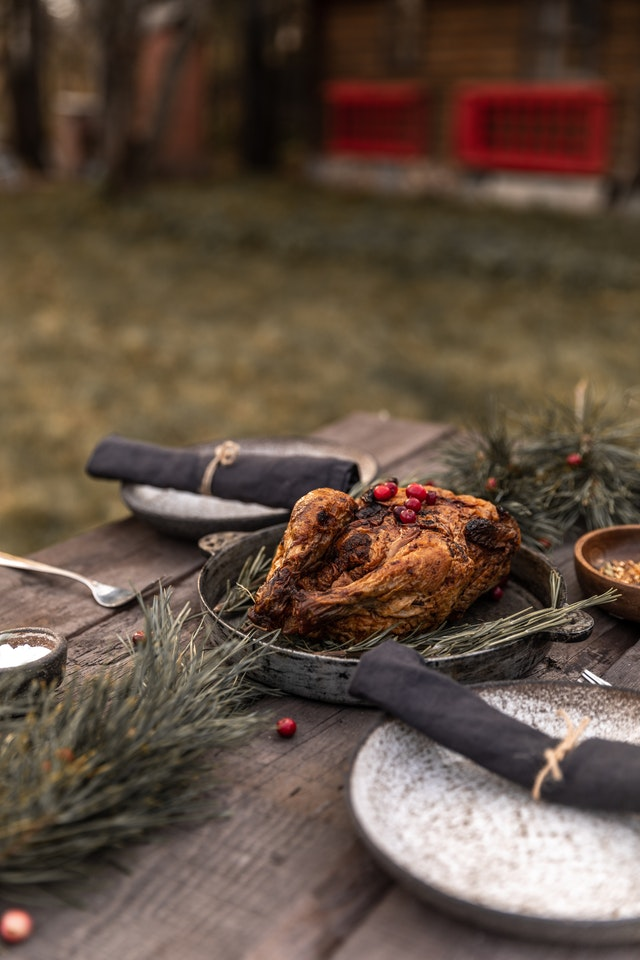 An outdoor table setting with a roasted turkey as a center piece