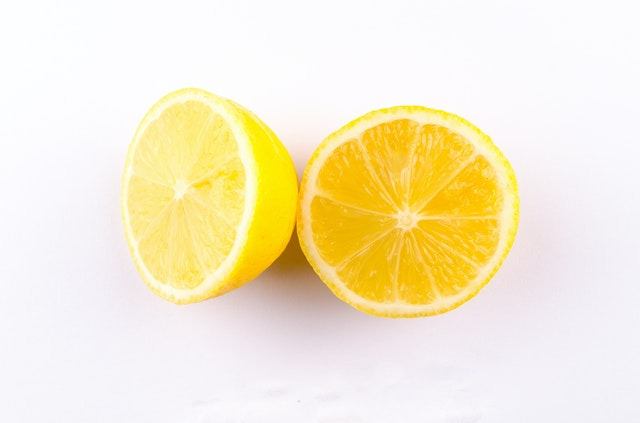 A lemon cut into two against a white background.