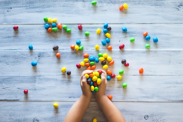 A child's hands arranging colorful candy on a wooden background.