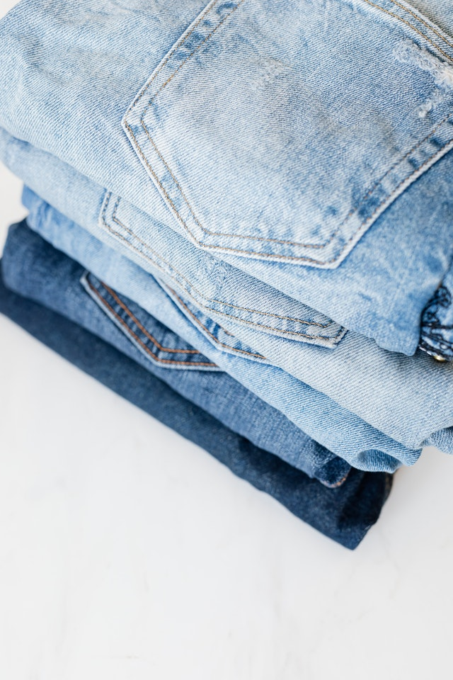 Five pairs of folded blue jeans.
