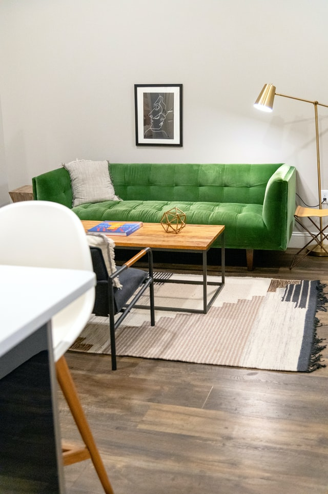A clean shot of a living room with a green couch