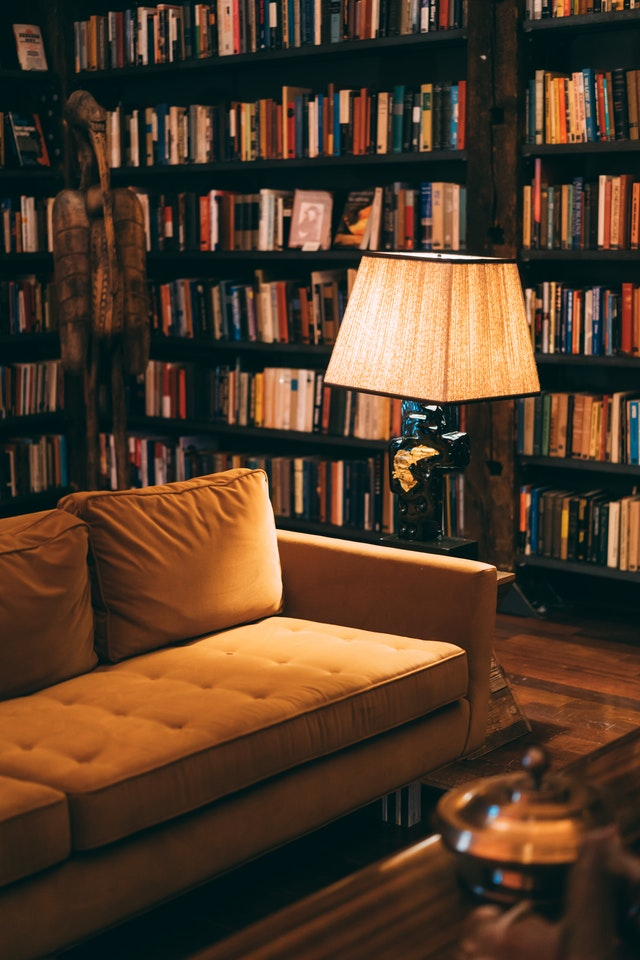 A reading nook surrounded by books on wall to ceiling shelves