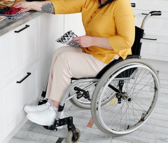 A woman sitting in a wheel chair reaching out to a kitchen counter