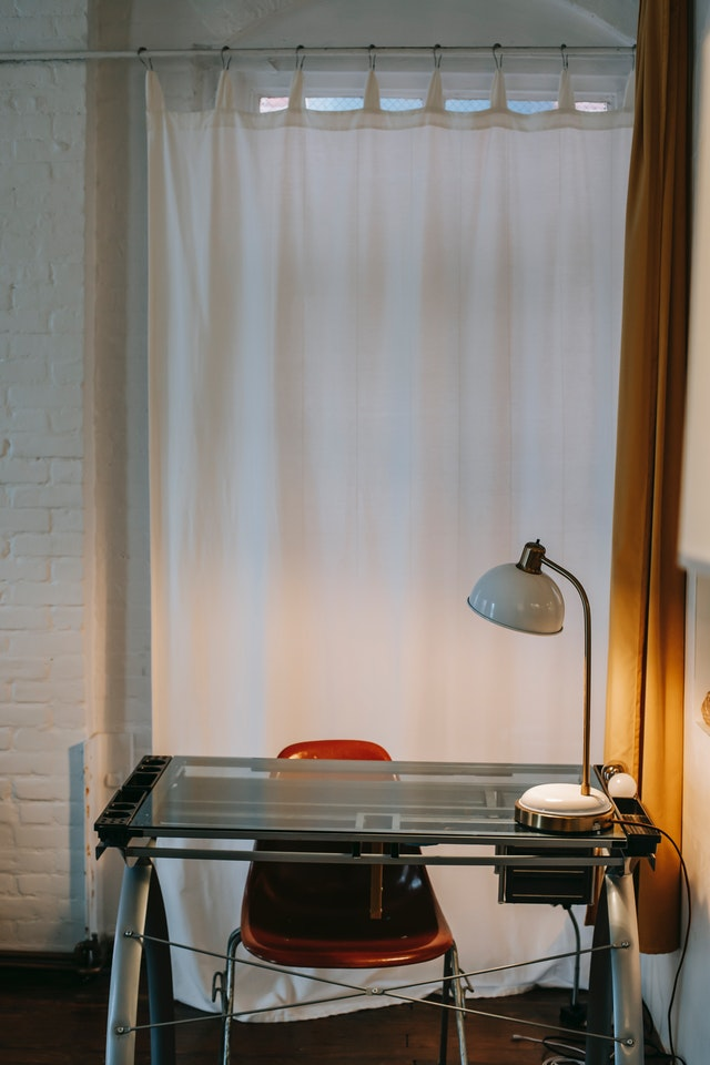 A white curtain sections off a work desk