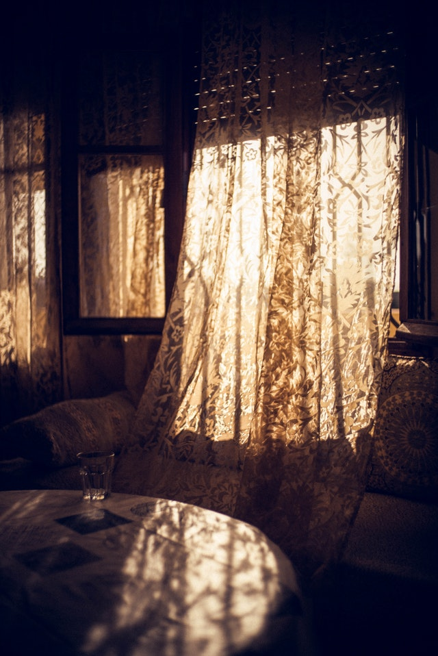 A white curtain lets in sunlights near a dinning area