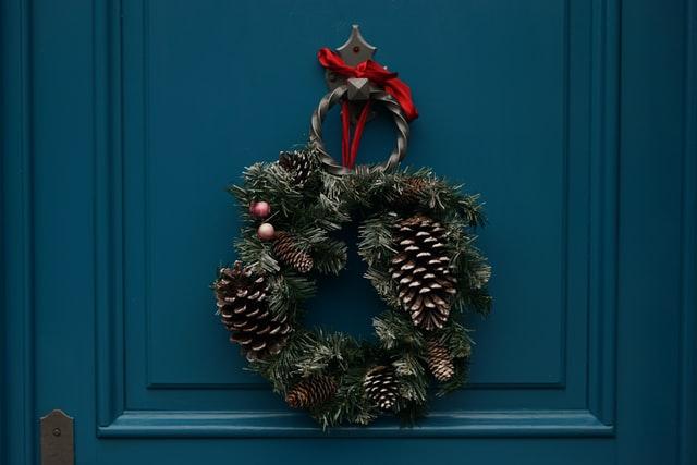 A festive wreath on a teal door