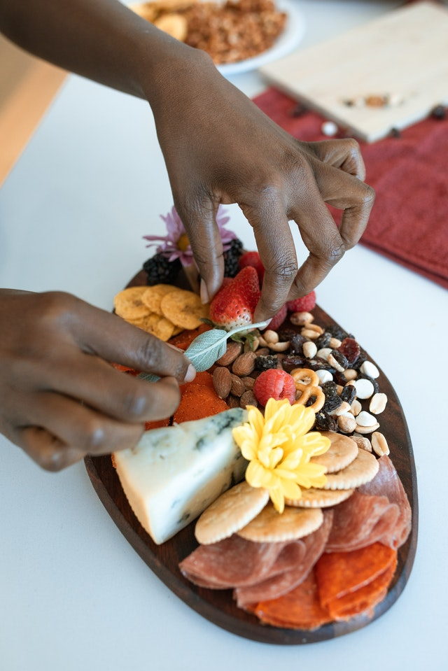 A hand adding basil leaf to a charcuterie and cheese board