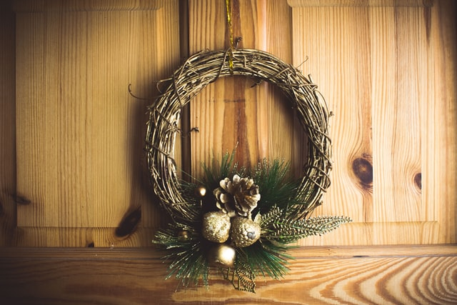 A wreath hanging on a wooden door.