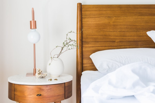 A wooden bed headboard and a nightstand next to it.
