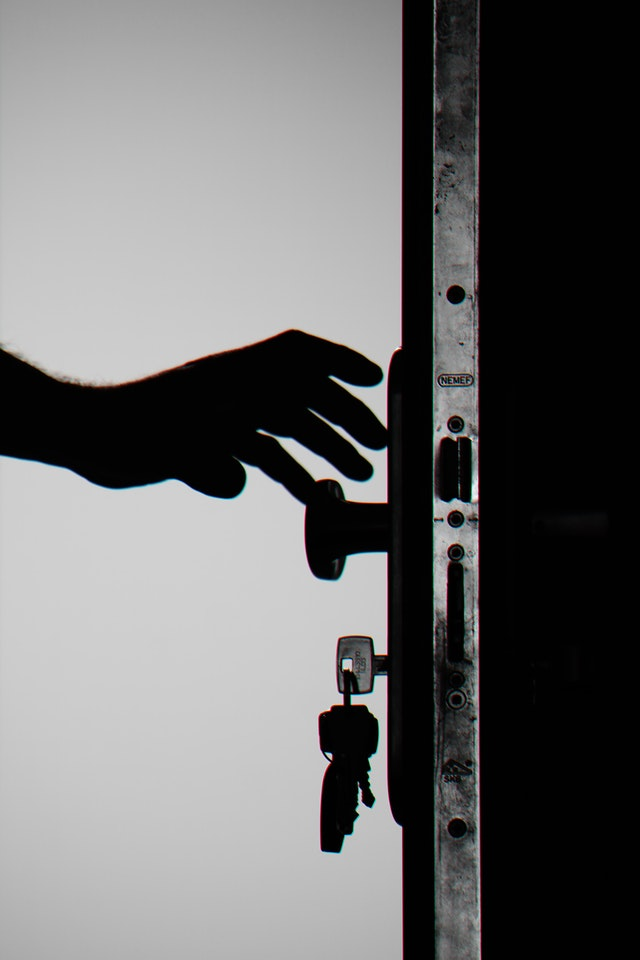 A hand reaching out to a door