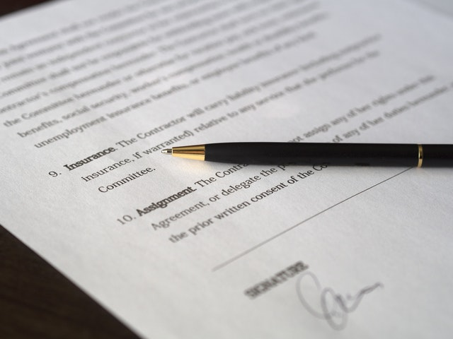 A lease agreement with a pen on top of it.
