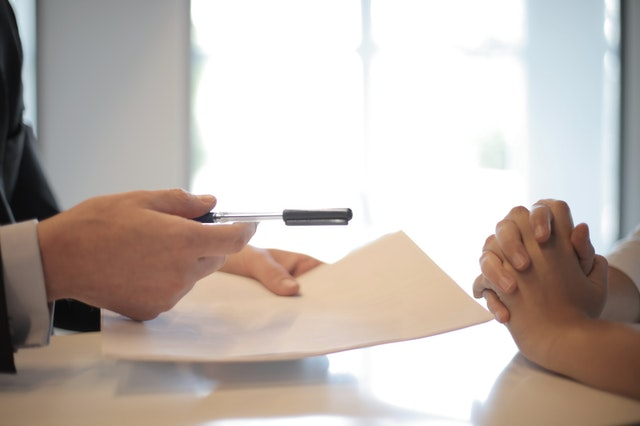 Two people sitting across from each other with one hand holding a pen and a paper