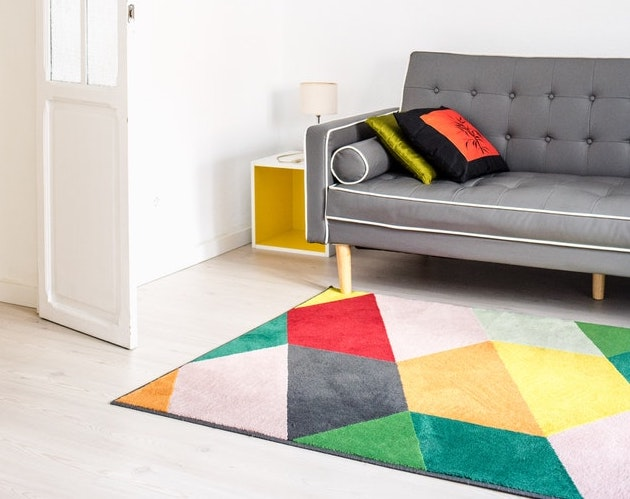 A bright rug laid out under a grey couch