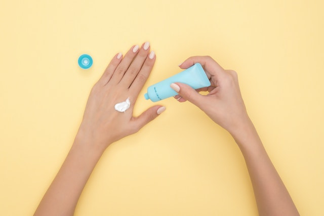 A yellow backdrop and two hands applying a lotion from a blue tube