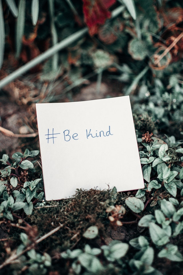 The words 'be kind' written on a post-it note