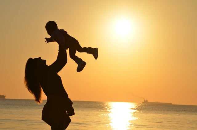 A child and a mom by a sunset near a ocean