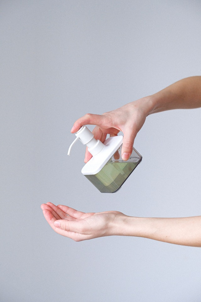 A hand using hand sanitizer