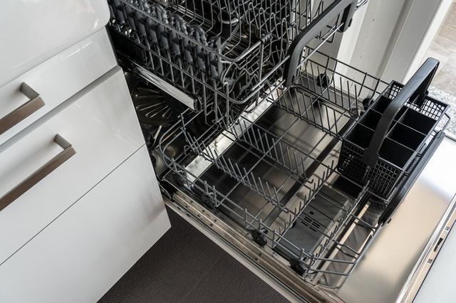 A clean, empty and open dishwasher